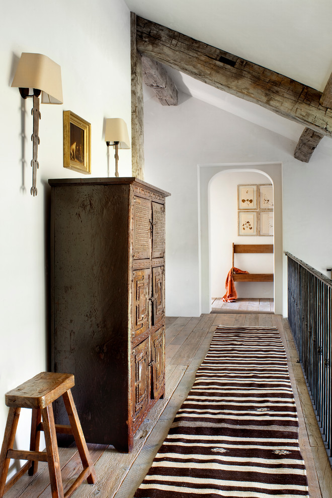Example of a mountain style medium tone wood floor hallway design in Other with white walls