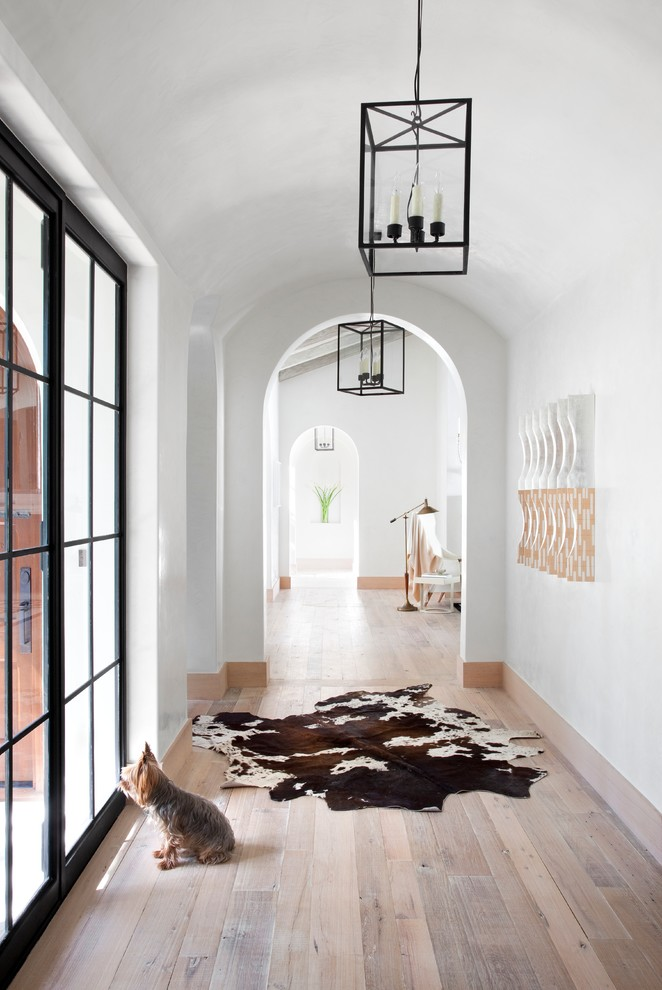 Example of a tuscan medium tone wood floor and beige floor hallway design in Austin with white walls