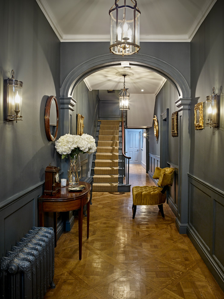 Mid-sized elegant light wood floor and beige floor hallway photo in London with gray walls