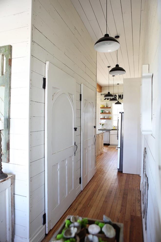 Hallway - cottage medium tone wood floor hallway idea in Austin with white walls