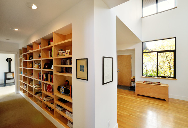 Example of a large trendy medium tone wood floor and yellow floor hallway design in Seattle with white walls