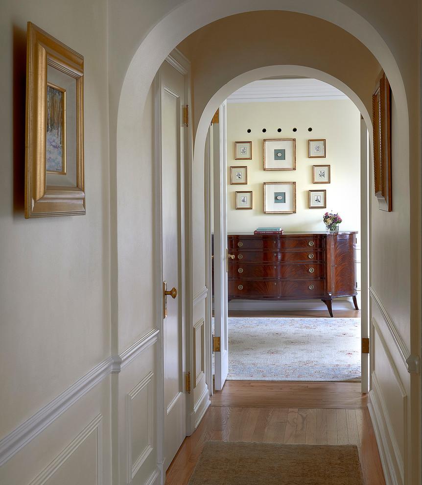 Réalisation d'un couloir tradition de taille moyenne avec un mur blanc et un sol en bois brun.