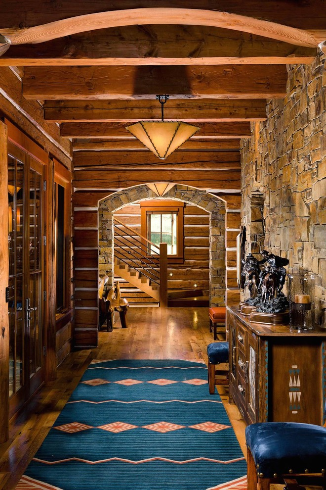 Large mountain style medium tone wood floor and brown floor hallway photo in Other with brown walls