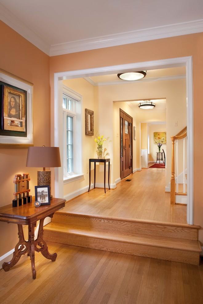 Hallway - traditional medium tone wood floor hallway idea in DC Metro with orange walls