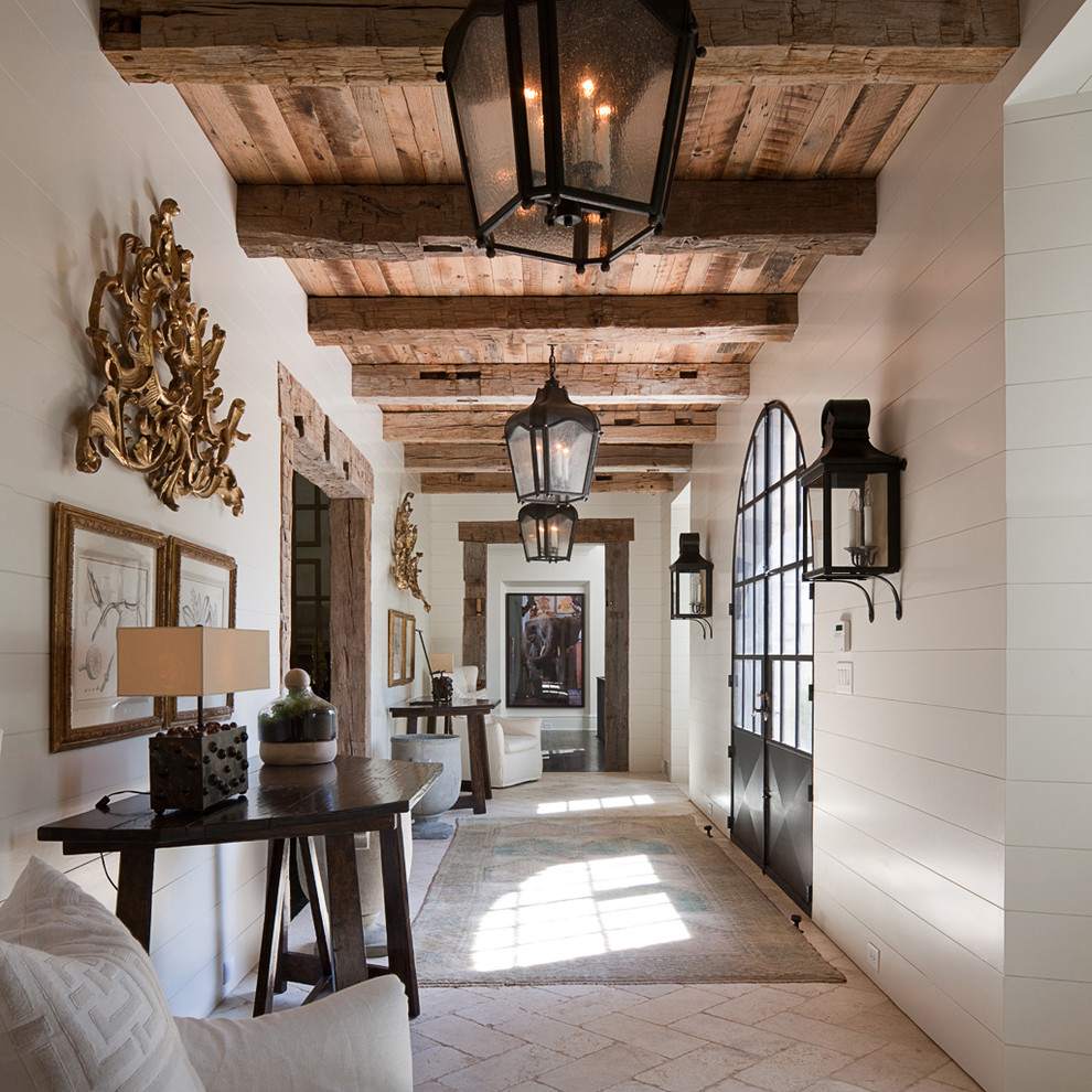 This is an example of a large mediterranean hallway in Atlanta with white walls, limestone floors and beige floor.