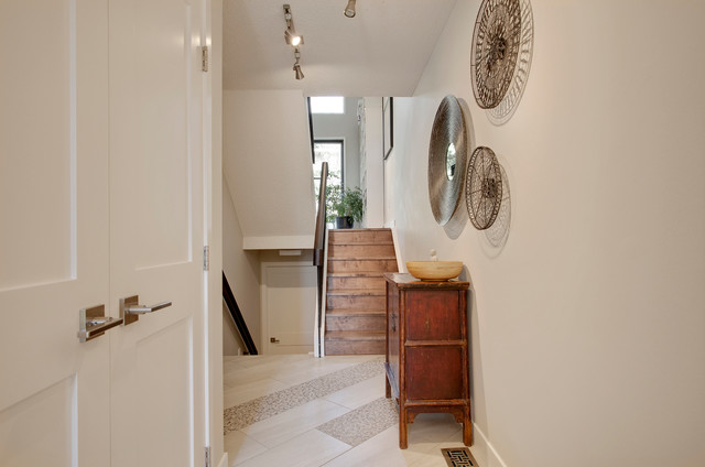 Inspiration for a contemporary ceramic floor hallway remodel in Calgary with beige walls