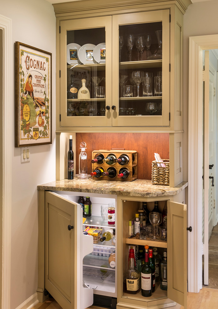 Inspiration for a small country single-wall medium tone wood floor home bar remodel in Chicago with beaded inset cabinets, beige cabinets, granite countertops and brown backsplash