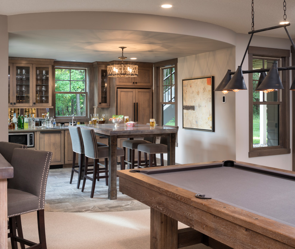 Inspiration for a large transitional u-shaped porcelain tile and gray floor wet bar remodel in Minneapolis with a drop-in sink, recessed-panel cabinets, brown cabinets, quartzite countertops and mirror backsplash