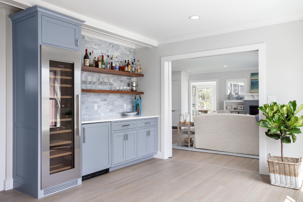 Beach style single-wall light wood floor and beige floor home bar photo in Boston with shaker cabinets, blue cabinets, gray backsplash and white countertops
