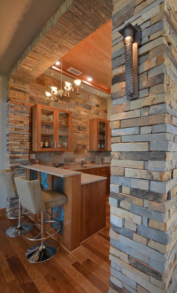 Example of a large transitional u-shaped medium tone wood floor seated home bar design in Austin with medium tone wood cabinets, multicolored backsplash and stone tile backsplash
