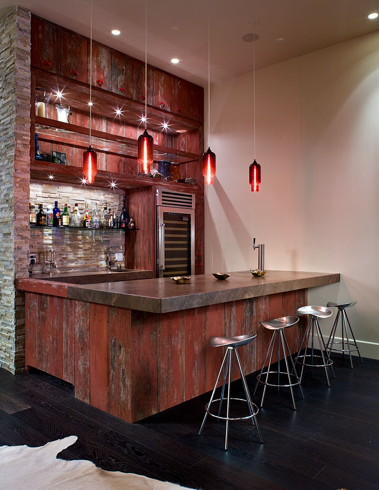 Example of a large urban galley dark wood floor and black floor seated home bar design in Las Vegas with distressed cabinets and multicolored backsplash