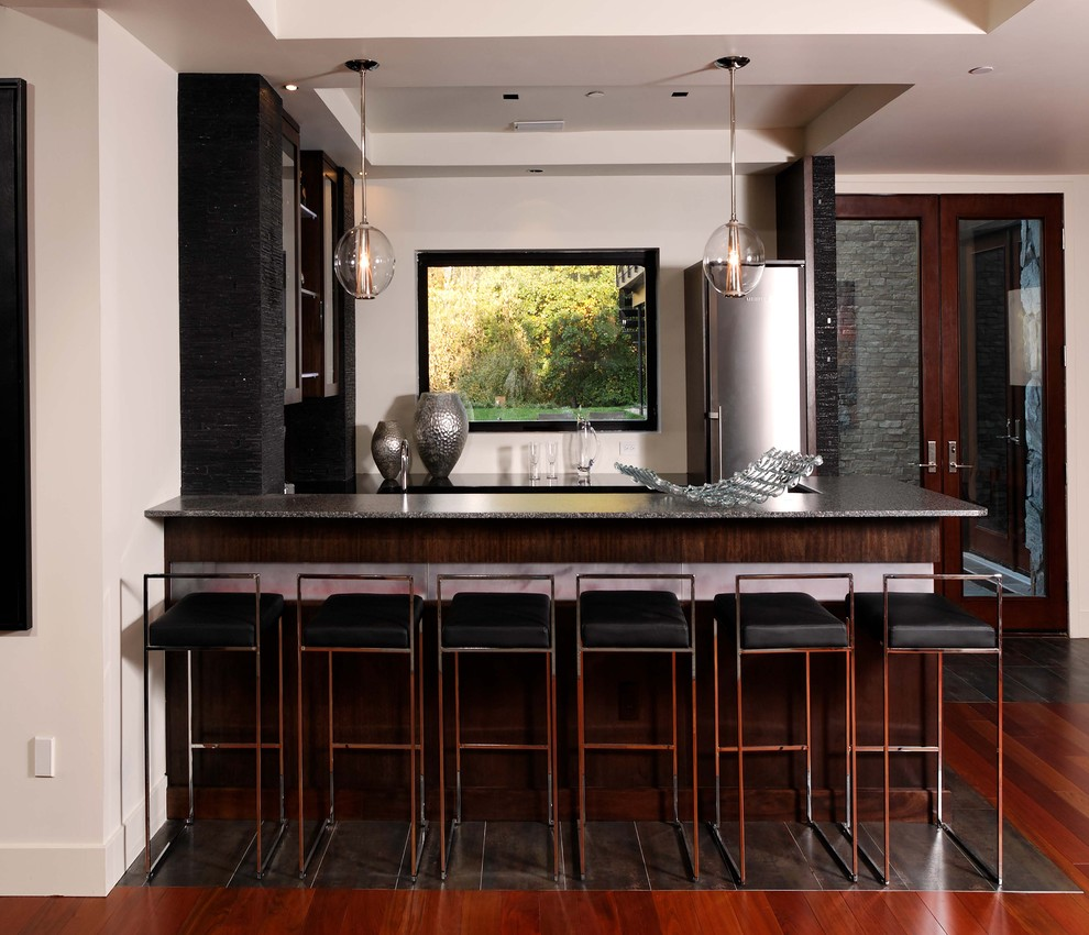 Seated home bar - large contemporary u-shaped dark wood floor and brown floor seated home bar idea in DC Metro with dark wood cabinets and granite countertops