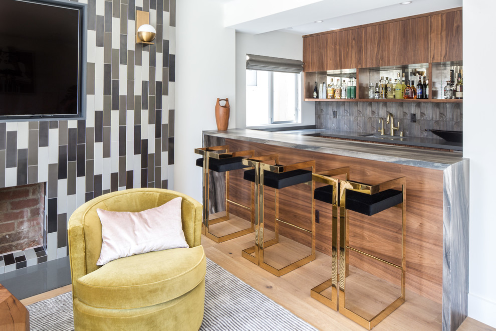 Example of a trendy galley light wood floor and beige floor seated home bar design in Los Angeles with an undermount sink, flat-panel cabinets, medium tone wood cabinets, gray backsplash and gray countertops