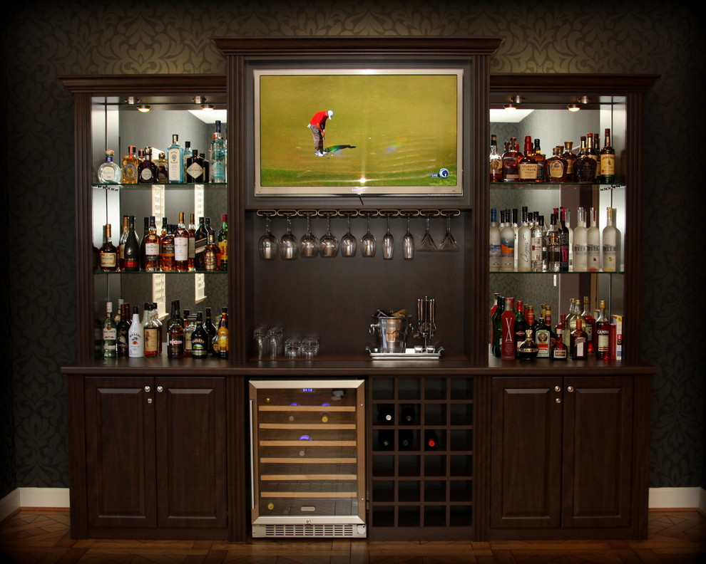 Home bar - mid-sized traditional single-wall medium tone wood floor and brown floor home bar idea in San Francisco with no sink, dark wood cabinets, laminate countertops, raised-panel cabinets and mirror backsplash