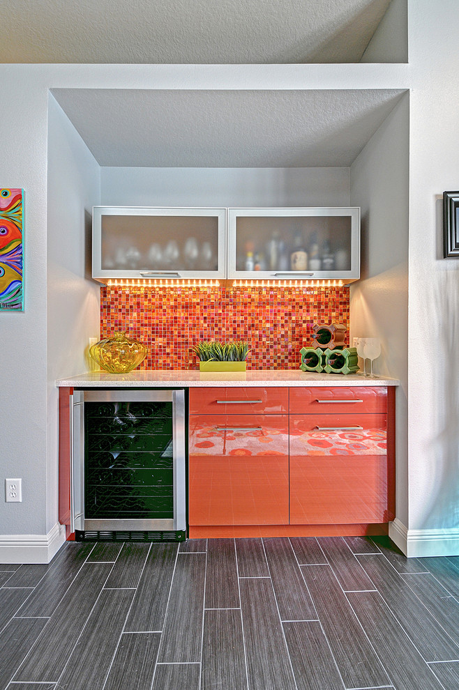 Example of a mid-sized trendy single-wall gray floor home bar design in Tampa with flat-panel cabinets, orange cabinets, multicolored backsplash and mosaic tile backsplash