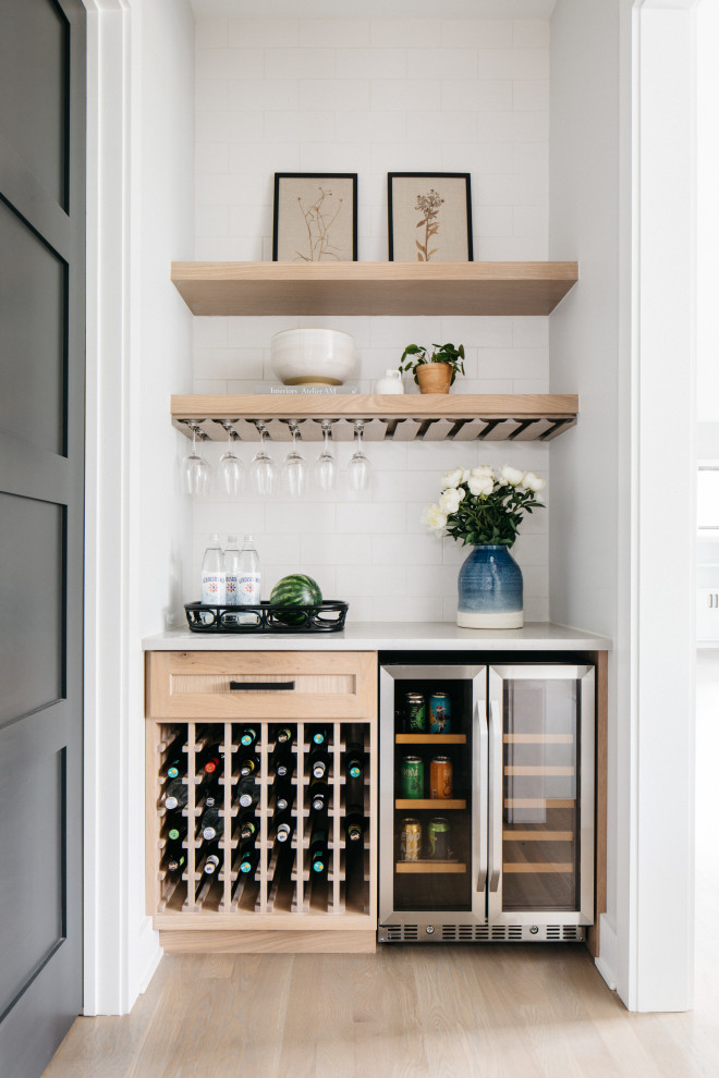 Inspiration for a transitional single-wall light wood floor and beige floor dry bar remodel in Chicago with no sink, shaker cabinets, light wood cabinets, marble countertops, white backsplash, subway tile backsplash and white countertops