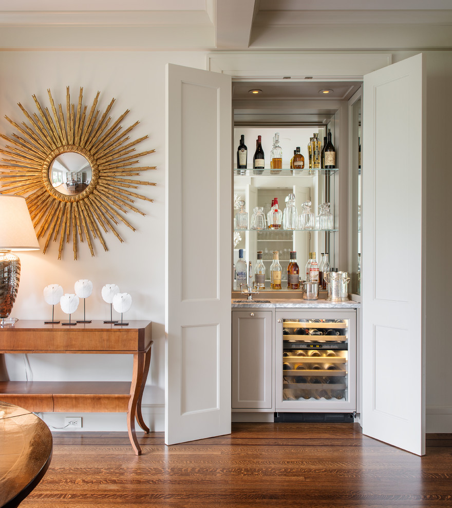 Wet bar - small transitional single-wall medium tone wood floor and brown floor wet bar idea in San Francisco with an undermount sink, recessed-panel cabinets, gray cabinets, mirror backsplash and white countertops