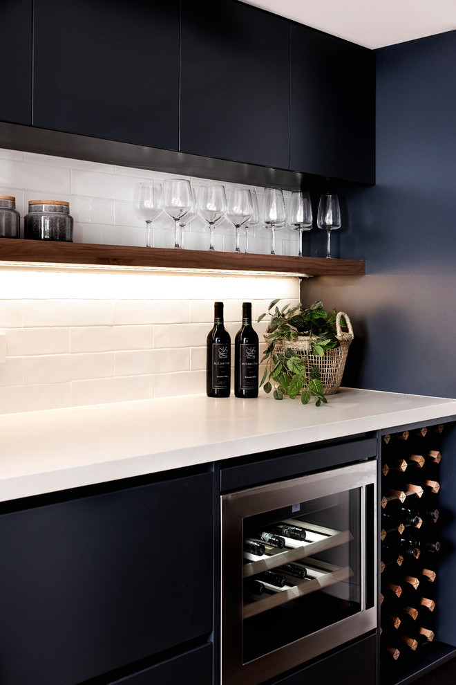 Inspiration for a mid-sized beach style single-wall home bar in Sydney with flat-panel cabinets, quartz benchtops, white splashback, white benchtop, subway tile splashback and black cabinets.