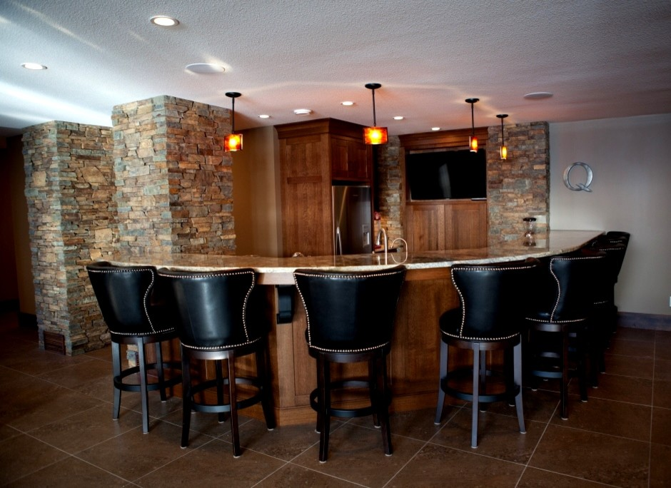 Large mountain style l-shaped seated home bar photo in Calgary with recessed-panel cabinets, dark wood cabinets and granite countertops