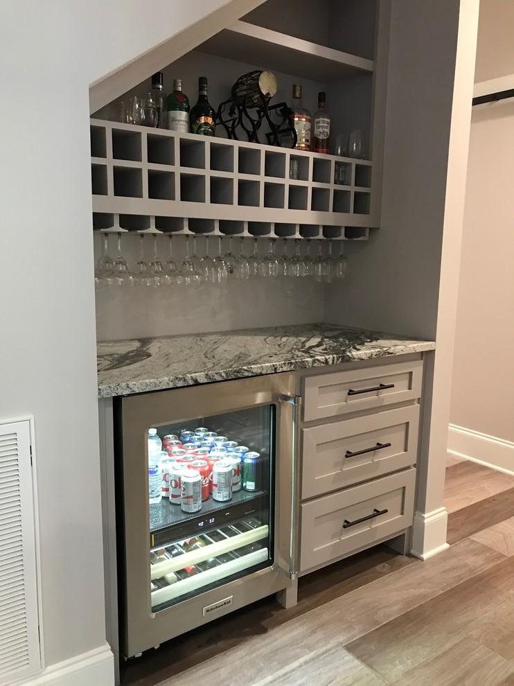 Idee per un piccolo angolo bar american style con ante in stile shaker, ante grigie, top in granito, paraspruzzi grigio, parquet chiaro e pavimento grigio