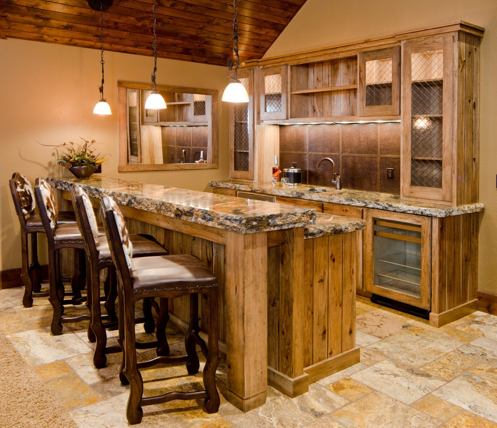 Example of a large classic galley travertine floor and beige floor seated home bar design in Other with an undermount sink, glass-front cabinets, medium tone wood cabinets, brown backsplash, granite countertops and brown countertops