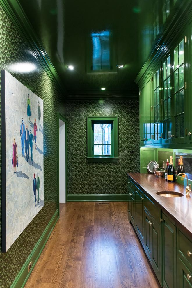 Large elegant single-wall brown floor and dark wood floor wet bar photo in Philadelphia with an undermount sink, raised-panel cabinets, green cabinets, wood countertops, mirror backsplash and brown countertops
