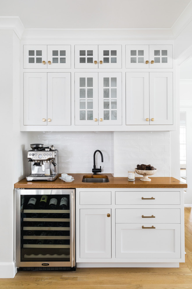 Small elegant single-wall light wood floor wet bar photo in Boston with an undermount sink, white cabinets, wood countertops, white backsplash, subway tile backsplash, brown countertops and shaker cabinets