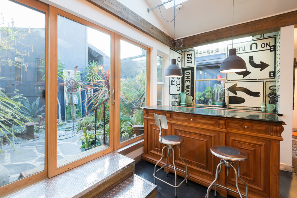 Small eclectic galley seated home bar photo in San Francisco with raised-panel cabinets and medium tone wood cabinets