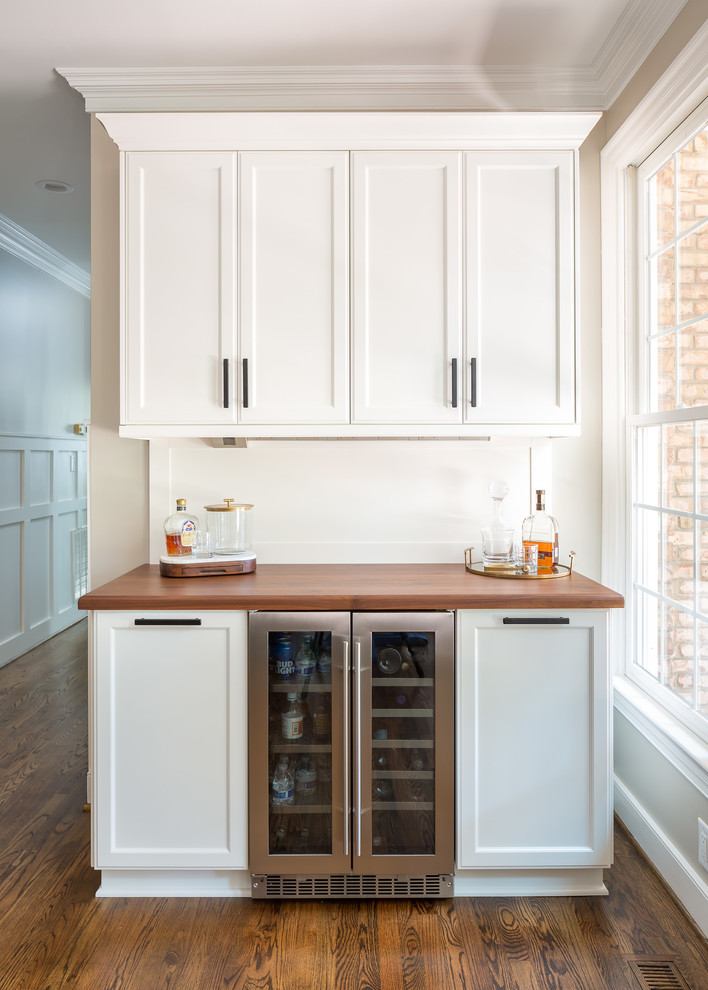 Inspiration for a transitional medium tone wood floor home bar remodel in Raleigh with shaker cabinets, white cabinets and wood countertops