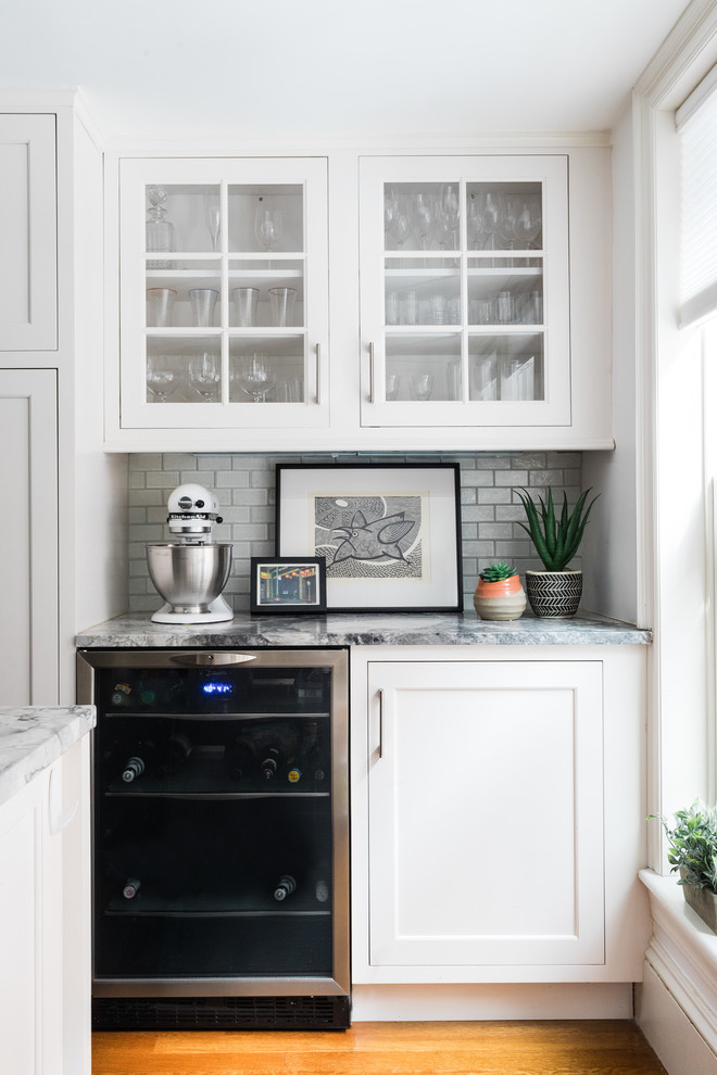Inspiration for a transitional medium tone wood floor home bar remodel in Boston with glass-front cabinets, white cabinets, white backsplash, subway tile backsplash and multicolored countertops