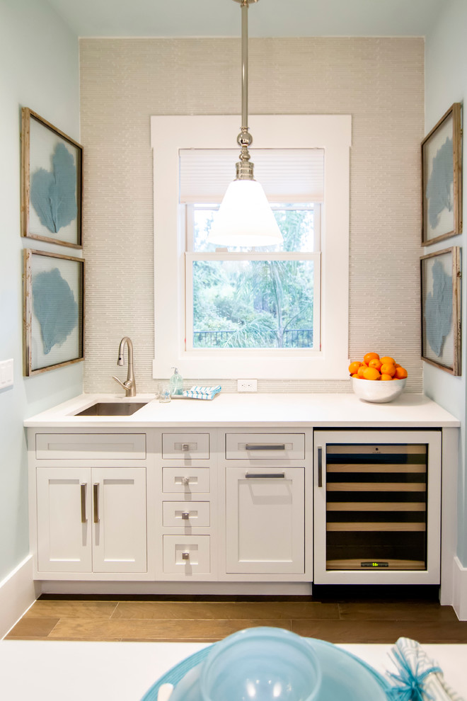 Example of a huge island style light wood floor and brown floor home bar design in Jacksonville with an undermount sink, white cabinets, granite countertops, white backsplash and recessed-panel cabinets