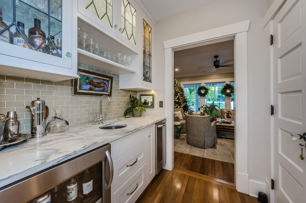 Inspiration for a transitional single-wall medium tone wood floor and brown floor wet bar remodel in Tampa with an undermount sink, shaker cabinets, white cabinets, gray backsplash, subway tile backsplash and gray countertops