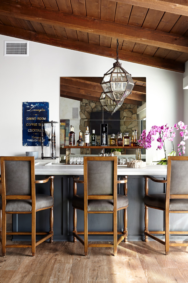 Traditional seated home bar in Los Angeles with mirror splashback, dark hardwood floors and white benchtop.