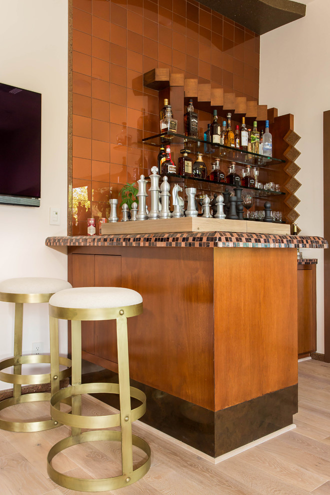 Home bar - mid-sized eclectic l-shaped light wood floor home bar idea in Los Angeles with a drop-in sink, flat-panel cabinets, medium tone wood cabinets, tile countertops and glass tile backsplash