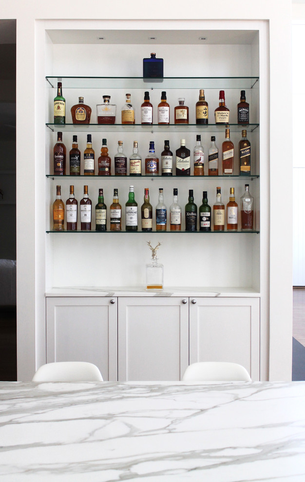 Home bar - transitional home bar idea in New York with white cabinets, marble countertops, white backsplash, subway tile backsplash and shaker cabinets