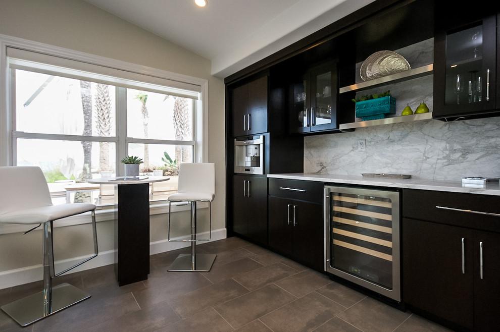 Modelo de bar en casa con fregadero lineal, tradicional renovado, con armarios con paneles lisos, puertas de armario negras, salpicadero blanco, salpicadero de losas de piedra y suelo marrón