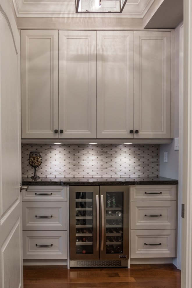 Inspiration for a mid-sized transitional single-wall medium tone wood floor home bar remodel in Toronto with shaker cabinets, granite countertops, mosaic tile backsplash, gray backsplash, white cabinets and no sink
