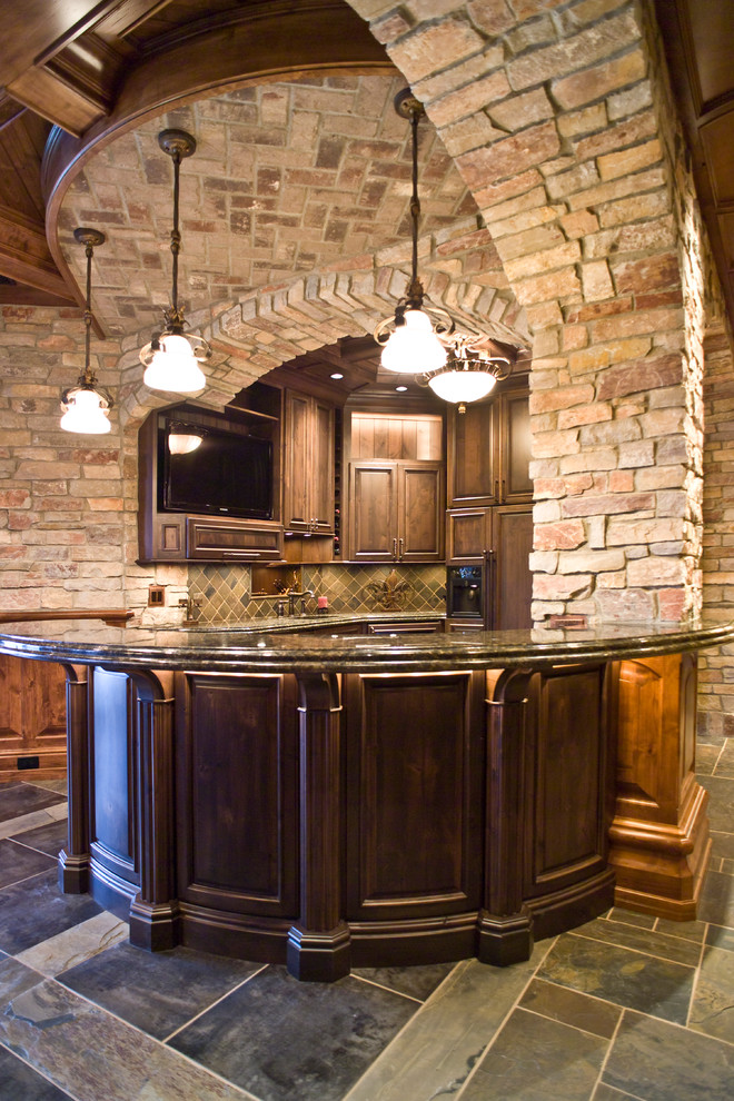 Inspiration for a timeless u-shaped home bar remodel in Other with raised-panel cabinets, dark wood cabinets and green backsplash