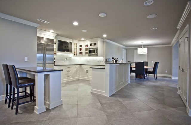 Seated home bar - huge transitional u-shaped porcelain floor and gray floor seated home bar idea in Other with shaker cabinets, white cabinets, white backsplash and black countertops
