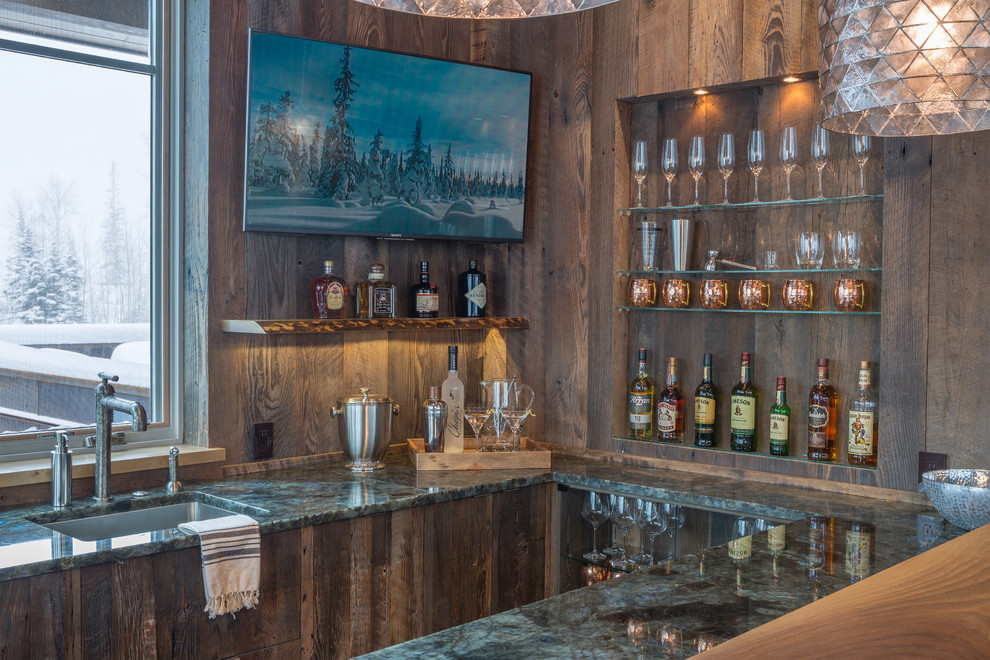 Seated home bar - mid-sized transitional u-shaped medium tone wood floor seated home bar idea in Denver with an undermount sink, flat-panel cabinets, distressed cabinets, granite countertops and brown backsplash
