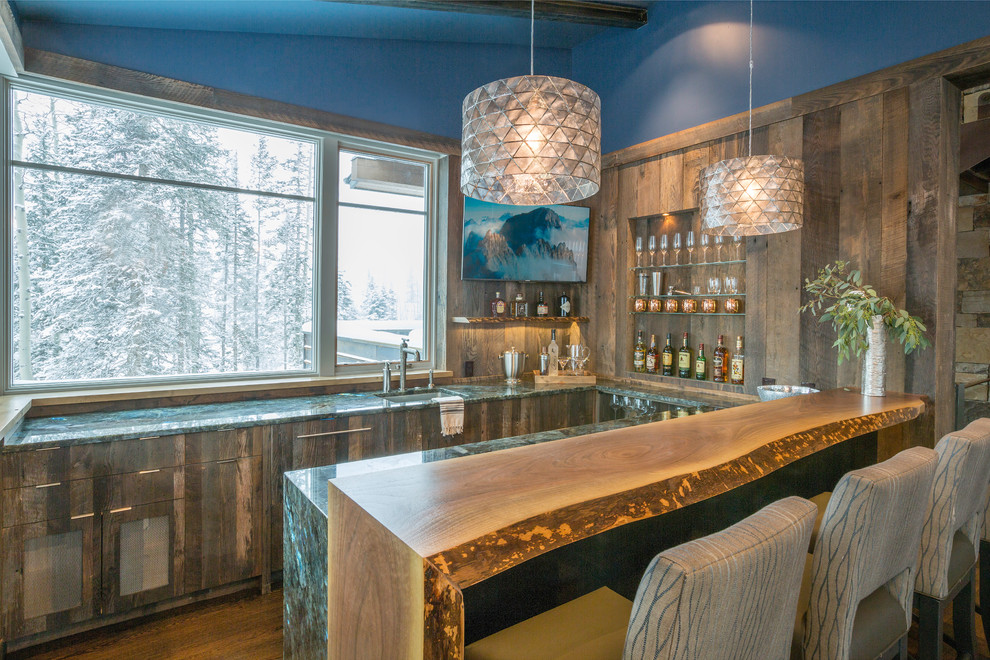 Inspiration for a mid-sized rustic u-shaped medium tone wood floor seated home bar remodel in Denver with an undermount sink, flat-panel cabinets, distressed cabinets, granite countertops, brown backsplash and turquoise countertops