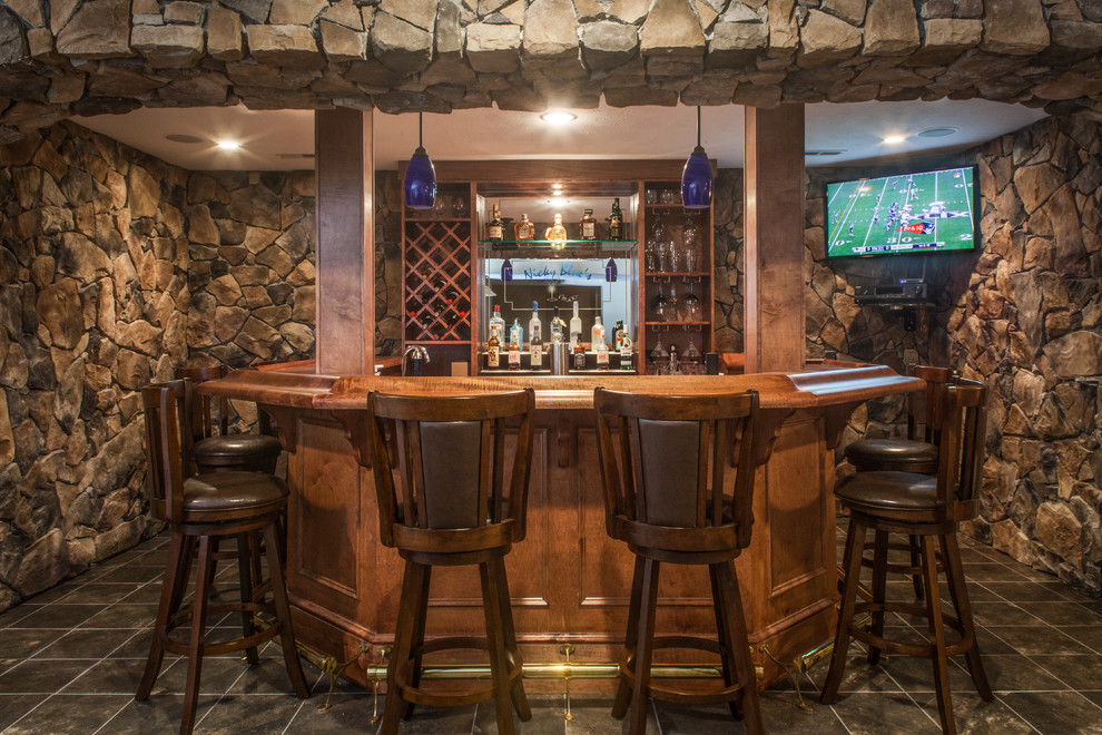Large mountain style u-shaped porcelain tile and gray floor seated home bar photo in Other with an undermount sink, raised-panel cabinets, medium tone wood cabinets, wood countertops, brown backsplash and stone tile backsplash