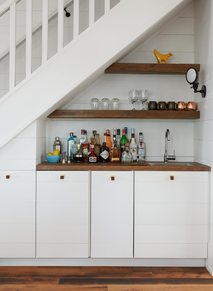 Inspiration for a small coastal single-wall medium tone wood floor and brown floor wet bar remodel in Toronto with wood countertops, white backsplash, brown countertops, flat-panel cabinets and white cabinets