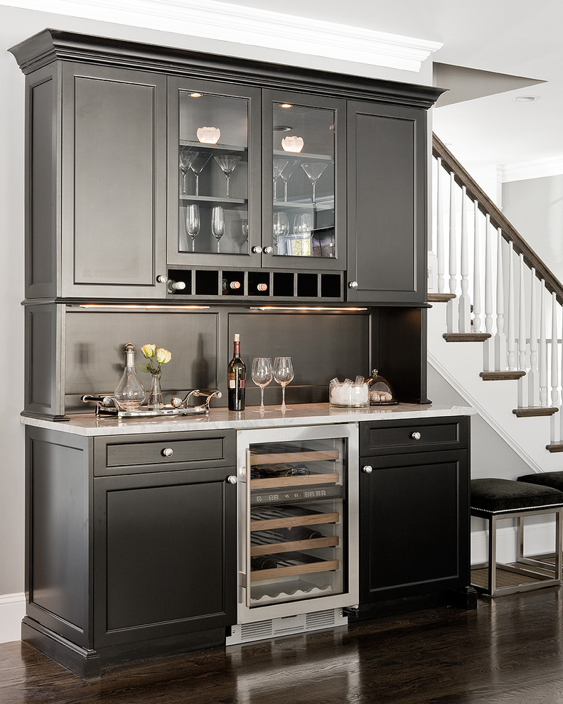 Home bar - traditional brown floor home bar idea in Boston with glass-front cabinets, black cabinets, granite countertops and white countertops