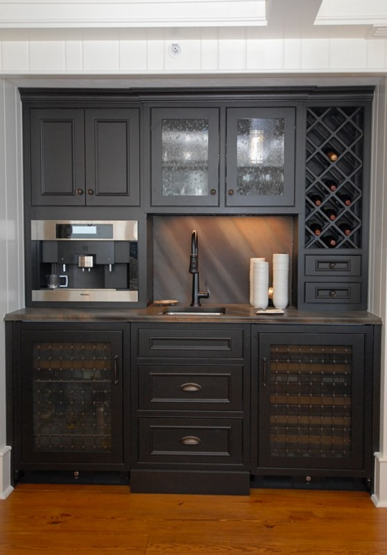 Wet bar - small traditional single-wall medium tone wood floor wet bar idea in Orlando with an undermount sink, recessed-panel cabinets, black cabinets, laminate countertops and multicolored backsplash