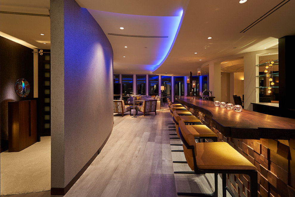 Example of a large trendy galley light wood floor and gray floor wet bar design in Other with dark wood cabinets and wood countertops