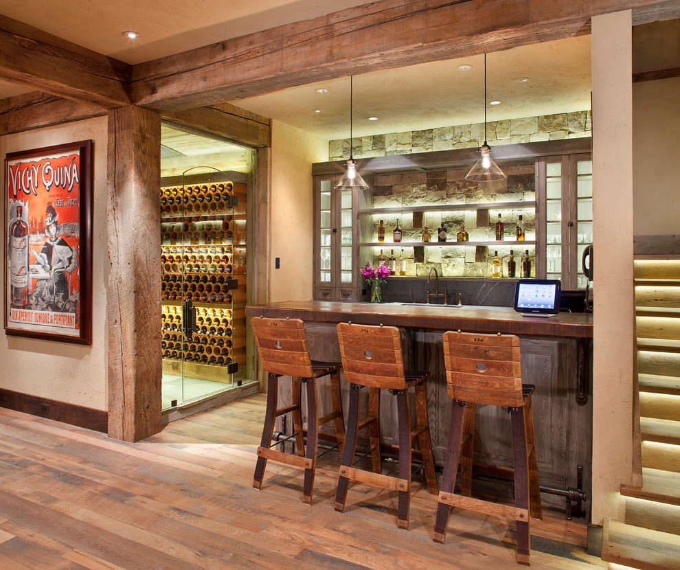 Seated home bar - mid-sized rustic medium tone wood floor seated home bar idea in Denver with glass-front cabinets, wood countertops, stone tile backsplash and brown countertops