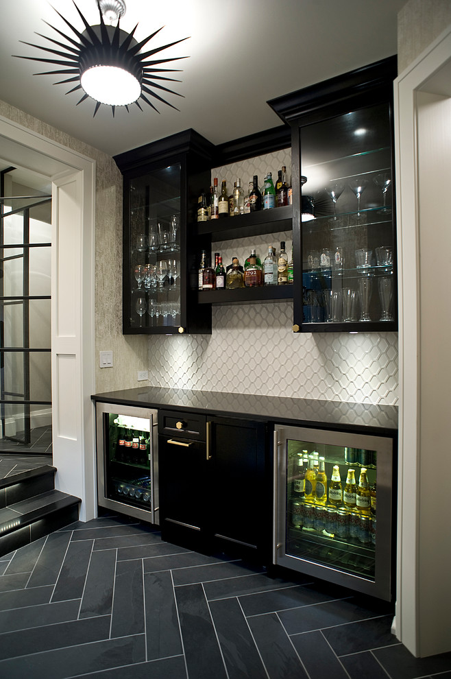 Home bar - transitional single-wall black floor home bar idea in Other with glass-front cabinets, black cabinets, white backsplash, no sink and black countertops