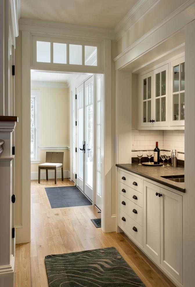 Large elegant medium tone wood floor home bar photo in Portland Maine
