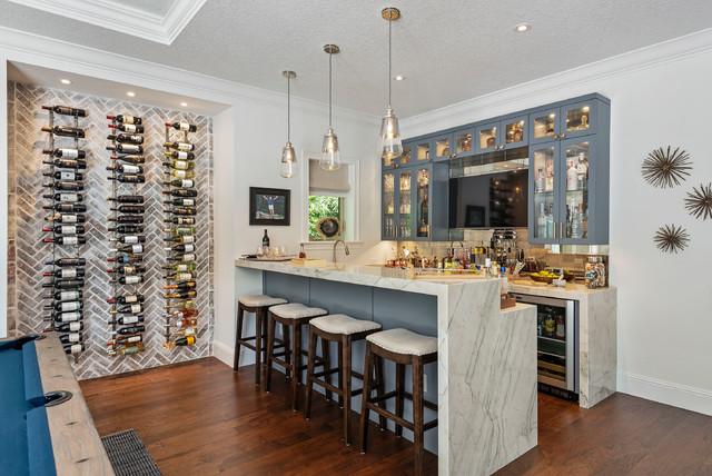 Coastal dark wood floor seated home bar photo in Orlando with glass-front cabinets, gray cabinets, marble countertops, metal backsplash and white countertops
